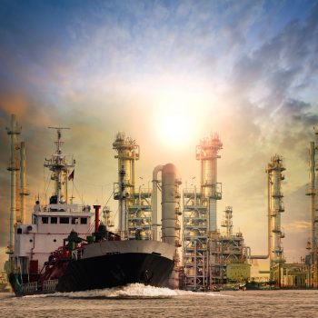 gas tanker ship and oil refinery plant background use for oil ,fuel energy and fossil power .transportation and heavy petroleum industry estate theme