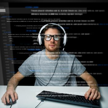 man in headset hacking computer or programming