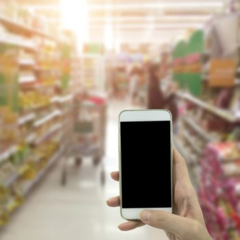 Female hand hold smartphone at supermarket and checking shopping list