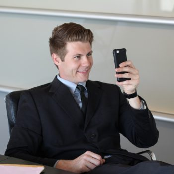 Businessman sitting inside modern office building looking at his mobile phone