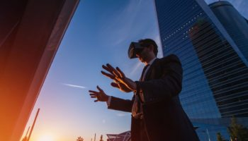 Businessman wearing virtual reality glasses and doing gestures with his hands outdoors. Modern business concept