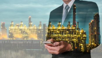 Double exposure of business man hand hold smart phone, mobile  and oil refinery industry plant, Electric Generating Factory in the night as communication of energy concept.