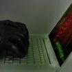 Hacker wearing black gloves using a laptop preparing an attack u