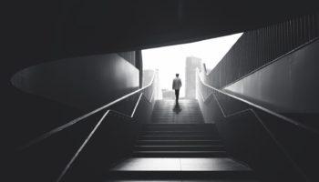Man raising stairs to reach the city