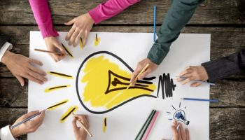 Six people, men and women, drawing bright yellow light bulb on a