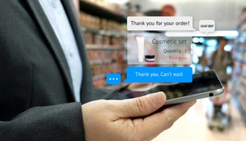 Chat bot and future marketing concept . Customer hand holding tablet for order cosmetic set and popup out tablet screen with automatic chatbot message screen , supermarket retail background