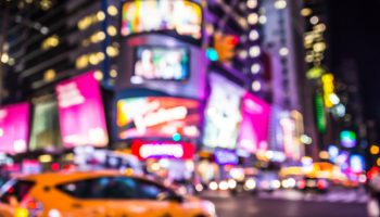 Defocused blur of Times Square in New York City with lights at night and taxi cab
