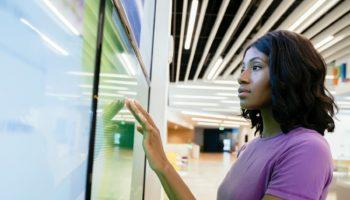 Woman touching large computer screen monitor
