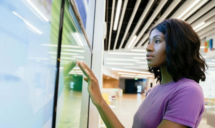 Woman touching large computer screen monitor