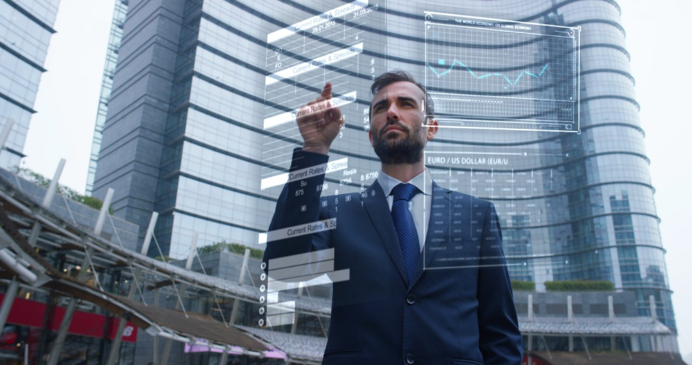 A businessman in a suit uses holography and augmented reality to see in 3D graphics financial economics and skyscraper in the background. Concept: immersive technology, business, economy, futuristic