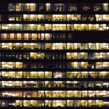 Full frame of silhouettes in illuminated windows of modern office building