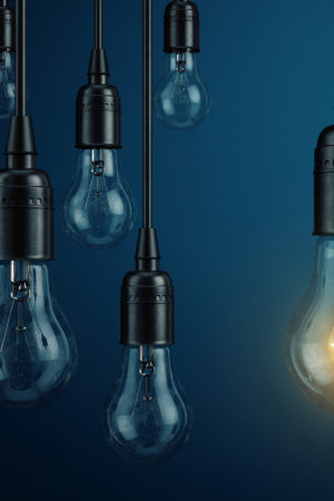 Unique, leadership, new idea concept – One light bulb lamp glowing different and standing out from o