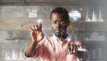 Double exposure. Black young businessman wearing glasses and casual shirt, touching futuristic screen interface with his fingers, making calculations, analyzing diagrams and schemes. Selective focus