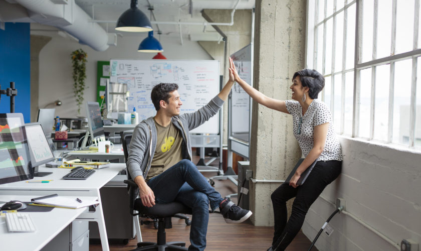 Full length of smiling casual man and woman cheering and high fiving in open modern office