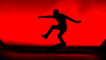 Silhouette of a young skater on a bright red background