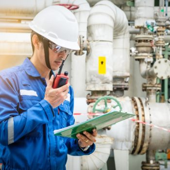 asian technician working with the walkie-talkie and checklist