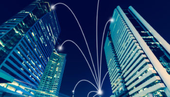 Smart city and internet line in blue tone, wireless communication network line on city commercial building background