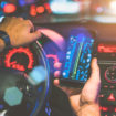 Cropped image. Closeup of smartphone in hand of young man sitting behind the wheel of modern car. Guy uses digital gadget. Man paves way to browser. On screen of smartphone map of area.