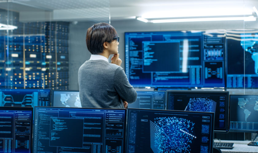 In the System Control Room Technical Operator Stands and Monitors Various Activities Showing on Multiple Displays with Graphics. Administrator Monitors Work of  Artificial Intelligence, Big Data Mining, Neural Network, Surveillance Project.