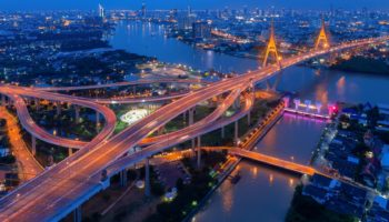 Top view over the highway,expressway and motorway at night, Aerial view interchange of a city, Shot from drone,Expressway is an important infrastructure in Thailand