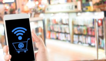 smartphone in hand with shopping cart wifi icon on blurred shopping mall modern technology store shop background