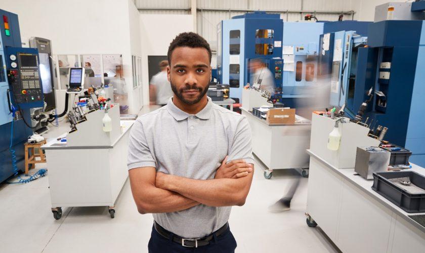 Portrait Of Male Engineer On Factory Floor Of Busy Workshop