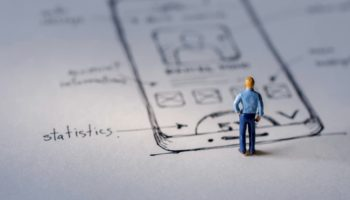 User Experience Concept. present by Miniature Figure of UX UI Designer standing on Paper of Interface Design Sketch