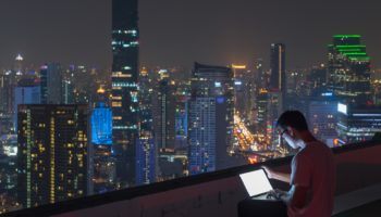 man using computer laptop on rootop at night
