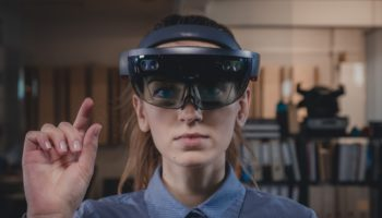 Portrait of young Caucasian female using augmented reality holographic hololens in modern office