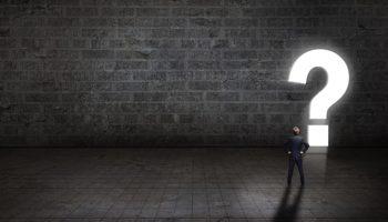 Geschftsmann steht vor einem leuchtenden Fragezeichen-Durchgang