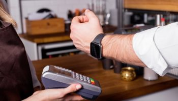 Person scanning smartwatch for payment