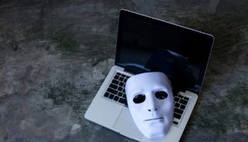 Anonymous mask to hide identity on computer laptop – internet criminal and cyber security threat concept